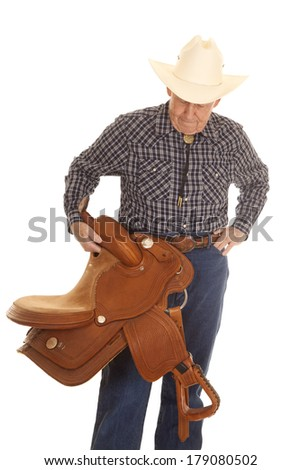 An old man standing holding a cowboy saddle. - stock photo
