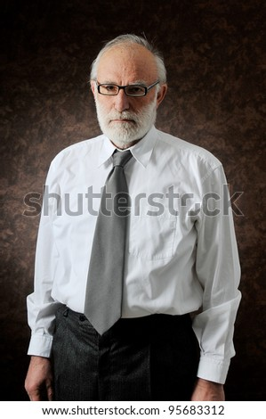 an old man wearing his glasses in studio - stock photo