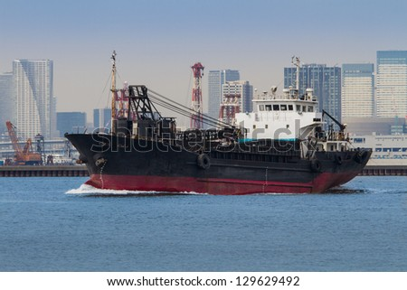 An old medium sized dredging ship cruises across the bay of a large city. - stock photo