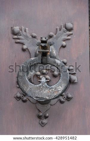 An old metal door handle knocker on a wooden door - stock photo