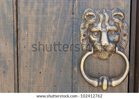 an old metal door handle knocker, on wooden door - stock photo