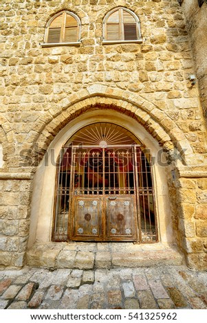 An old metal gate in the yellow brick wall. Old city Jaffa, Israel.