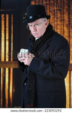 An old Mr. Scrooge in his top hat and scarf scowling at the viewer while holding a fistful of hundred-dollar bills close to his chest. - stock photo