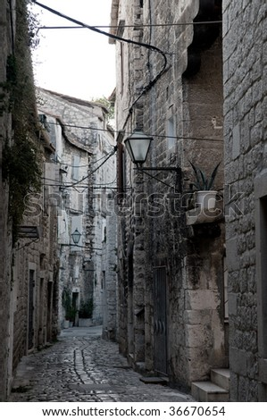 An old narrow street is in Croatia, city Trogir. - stock photo