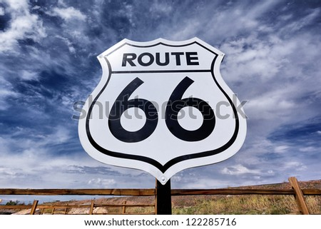 An old, nostalgic route 66 sign and sky - stock photo