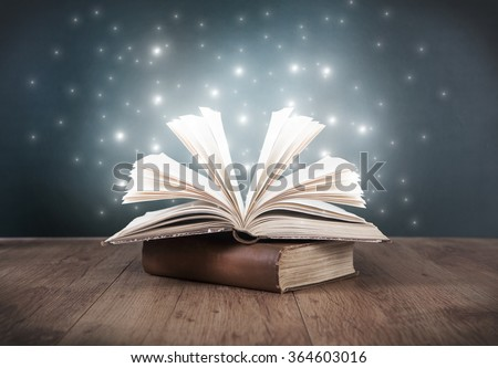 an old open book on a table in front of a blackboard - stock photo