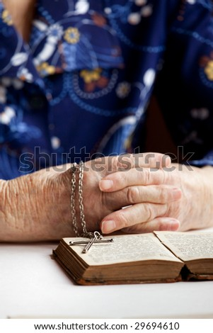 An old pair of hands with a book and cross - shallow depth of field with focus on cross - stock photo