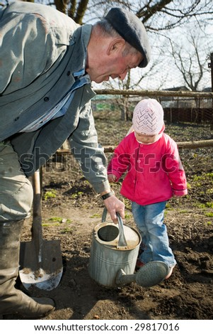 An old peasant teaching his little granddaughter to work in the kitchen garden