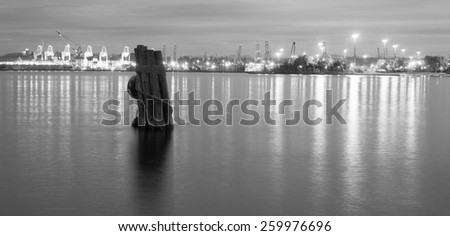 An old piling is seen in the foreground in this black and white portrait of the Post of Seattle - stock photo