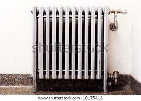 An old radiator with a new thermostat - stock photo