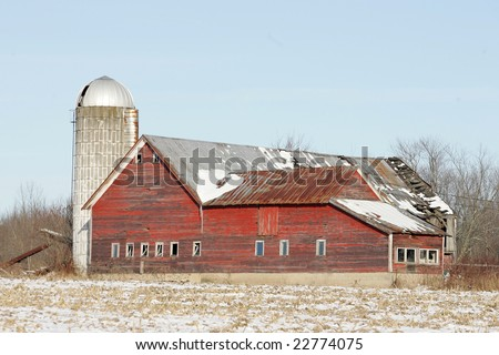 An old Red Barn and silo on a Farm during the winter