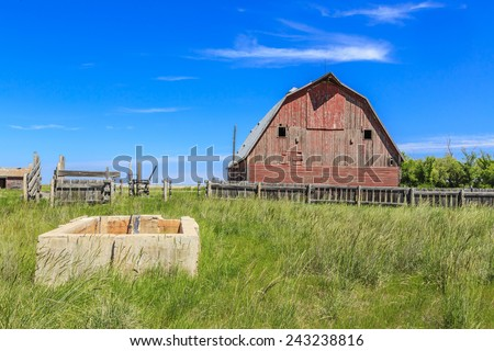 An old red barn in a farm yard in summer - stock photo