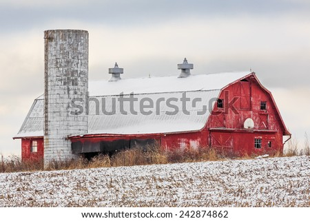 An old red barn with basketball hoop and silo stands in a snowy field on a cloudy day. - stock photo