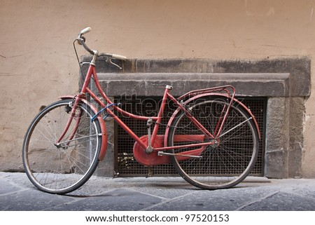 An old red bike laid on a wall - stock photo