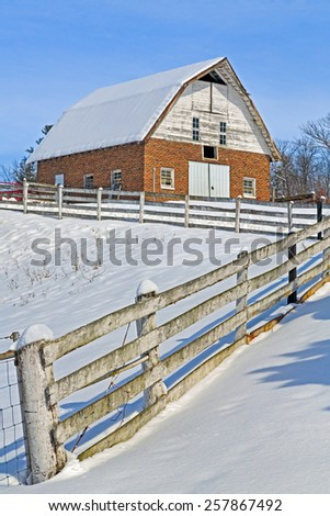 An old red brick barn and a rugged white fence are covered in winter snow on a sunny day. - stock photo