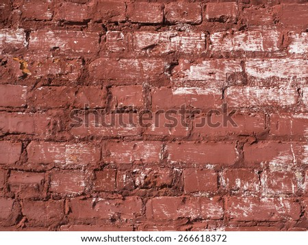 An old red  brick wall with white pain splashes. - stock photo