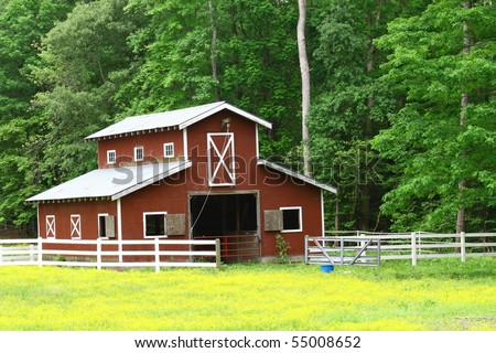 An old red horse barn in the woods - stock photo