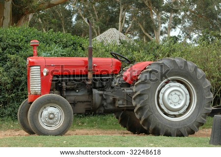 An old red tractor standing on a farm outdoors