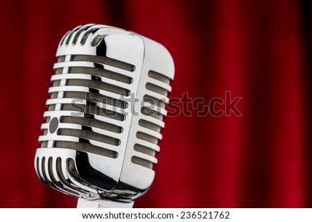 an old retro microphone in front of red velvet background. - stock photo