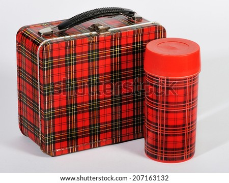 An old retro plaid lunchbox and thermos. - stock photo