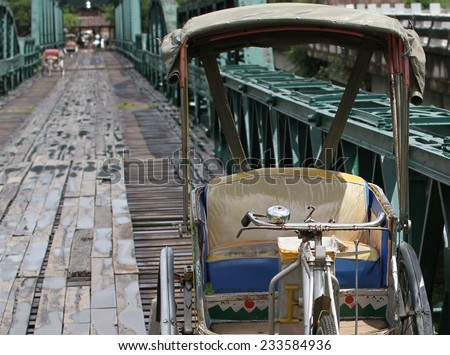 An old rickshaw on the Memorial Bridge over the Pai River built in 1942 by the Japanese during World War II to transport goods to Myanmar, near Chiang Mai, Thailand.  - stock photo