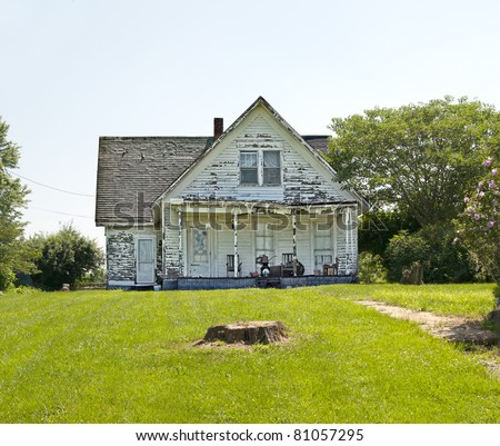 An old run down, weather beaten wood siding house that is in need of repair.  What a realtor would refer to as a fixer-upper. - stock photo