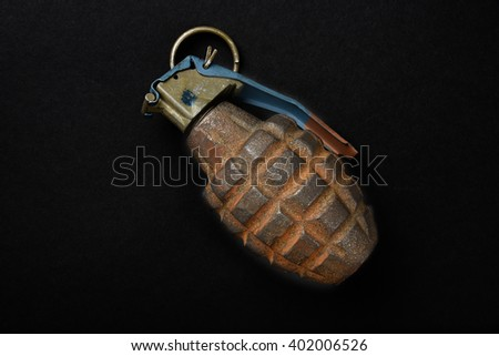 An old, rusted hand grenade on a black background - stock photo