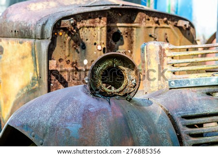 An old rusted out truck with missing headlight - stock photo
