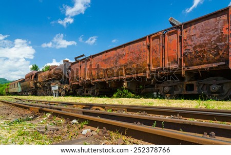 An old rusty abandoned steam locomotive with carriage cars (wagons) standing on an unused railway with dry grass and blue sky. - stock photo