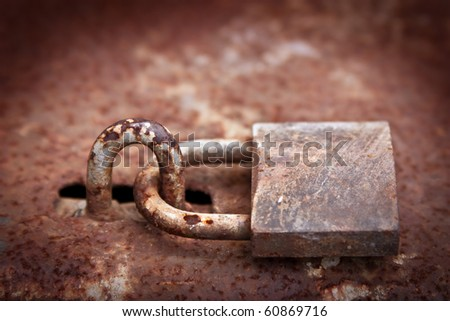 an old rusty lock hanging on the gate - stock photo
