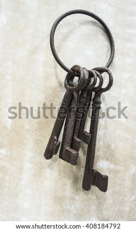An old rusty ring of five large rusty keys on a background of distressed material.