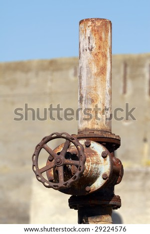 An old, rusty tap in a factory - stock photo