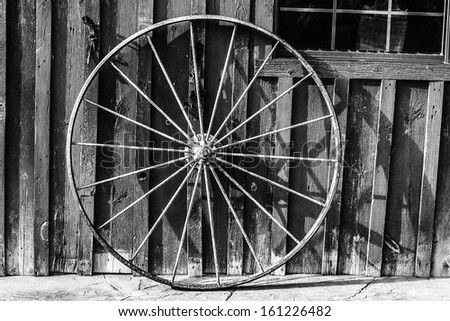 An old rusty wagon wheel leaning on a barn wall in black and white - stock photo