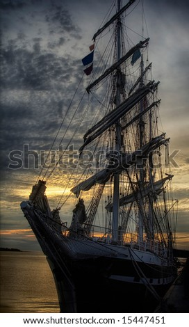 An old sailing ship at dockside at sunset. - stock photo