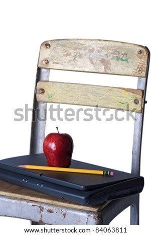 An old school chair holding a closed laptop with a red apple and sharp pencil on the seat, against a 255 white background. - stock photo