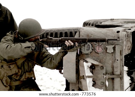 An old, sepia, and grainy WWII photo of an American Soldier firing a rifle - stock photo