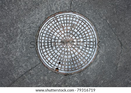 An old sewer manhole cover surrounded by an asphalt street - stock photo