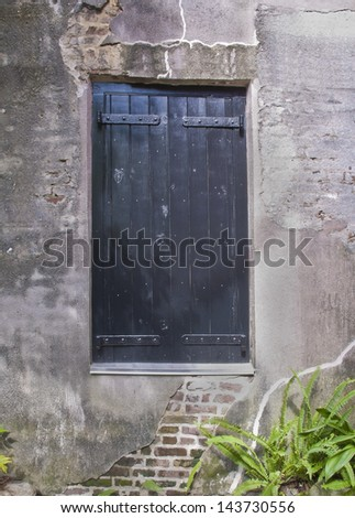 An old shuttered window in the stucco wall of an eighteenth century alley or street.