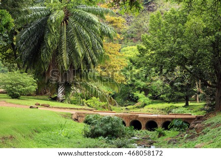 An old stone bridge crosses a creek in a beautiful, wet, green landscape.