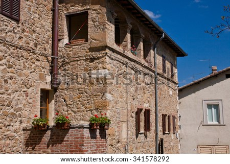 An old stone building and red flowers in San Quirico d'Orcia in Italy