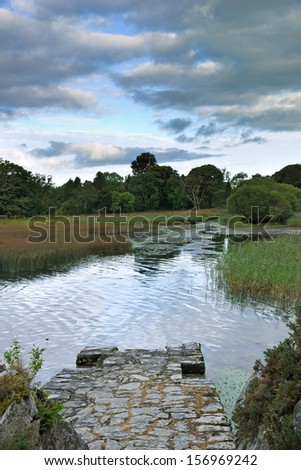 An old stone pier on Lough Leane in Killarney National Park, Ireland. Reeds and rushes line the lake shore, reflected in the calm water on a summer morning. - stock photo