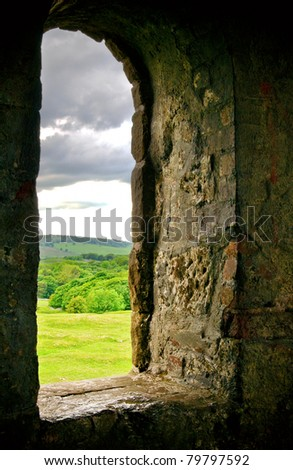 an old stone window looking out onto countryside