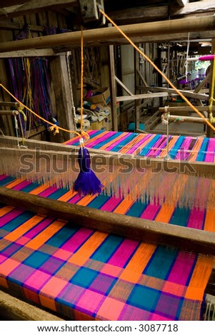 An old-style loom producing a colorful cloth - stock photo