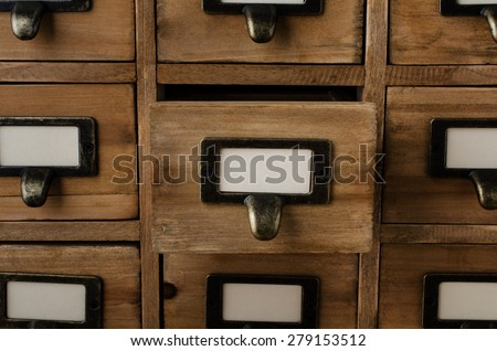 An old style wooden cabinet of library card index drawers with label holders and blank labels facing front.  One drawer in the middle is opened. - stock photo