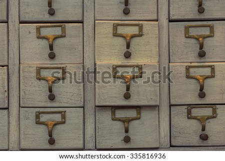 An old style wooden cabinet of library card index drawers with label holders and blank labels facing front - stock photo
