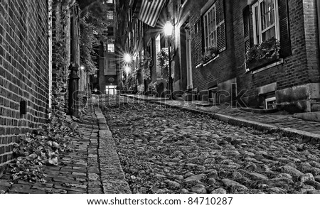 An old 19th Century cobble stone road in Boston Massachusetts, Lit only by the gas lamps revealing the shuttered windows and brightly lit doorways of the rowhouses on Acorn Street. - stock photo