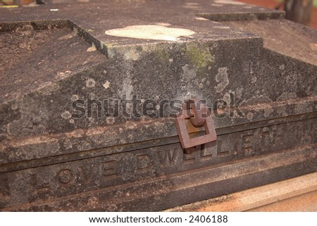 "An old tomb with a cross top, and iron fittings. Very vampiric. Inscription ""Love dwelleth"" - stock photo"