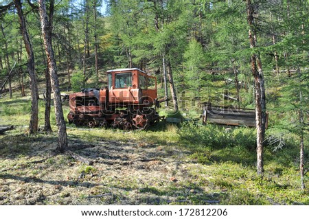 An old tractor, lost and asleep in the forest in Eastern Yakutia on the shore of the nameless lake.
