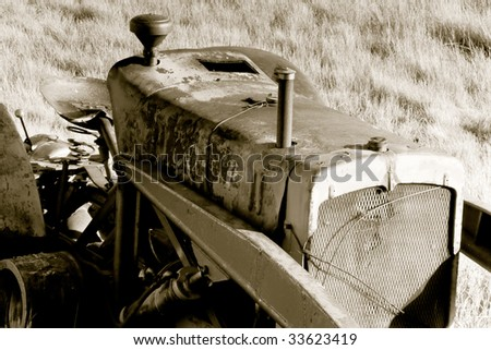 An old tractor rusting away on the prairie landscape.  Sepia tone applied to photo. - stock photo