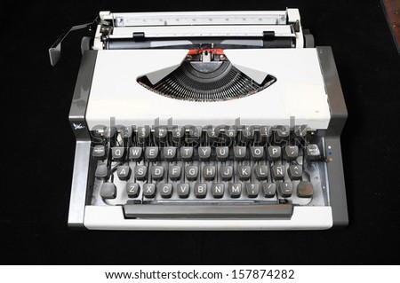 An Old Travel Vintage Typewriter on a Black Background - stock photo